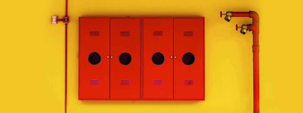 Red lockers and pipes on yellow wall